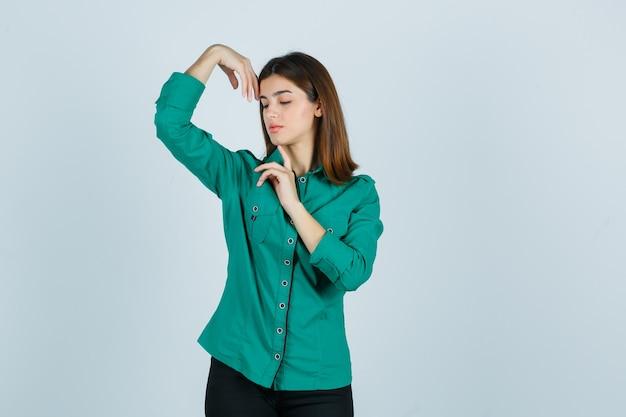 Jonge vrouw poseren met handen rond hoofd in groen shirt en op zoek sierlijk, vooraanzicht.