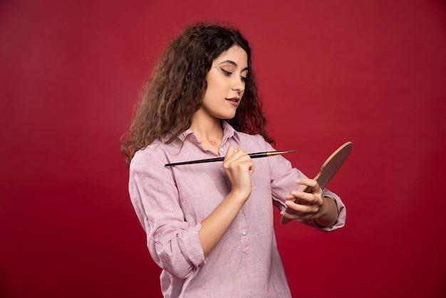 Jonge vrouw poseren met kwast en verfpalet.