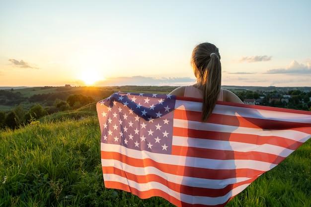 Jonge vrouw poseren met usa nationale vlag buiten bij zonsondergang. positief meisje dat de onafhankelijkheidsdag van de verenigde staten viert.