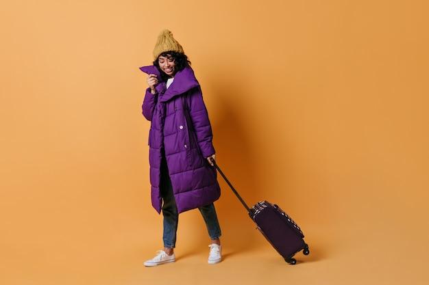 Jonge vrouw poseren met valise lachen
