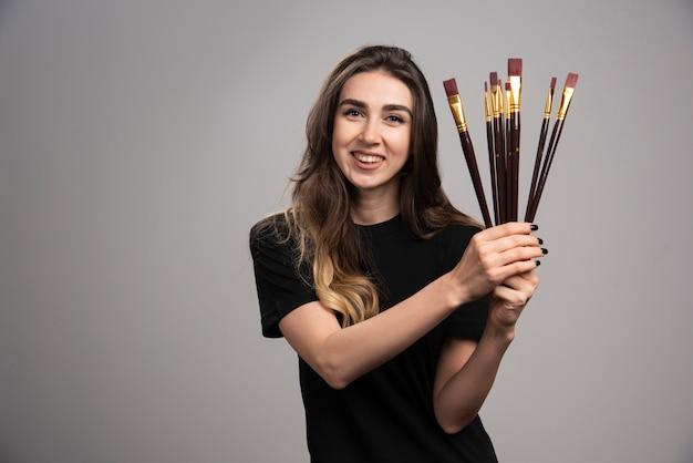 Jonge vrouw poseren met verfborstels op grijze muur.