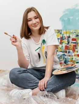 Jonge vrouw poseren naast haar kleurrijke schilderij