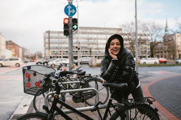 Jonge vrouw poseren op een parkeerplaats met fietsen