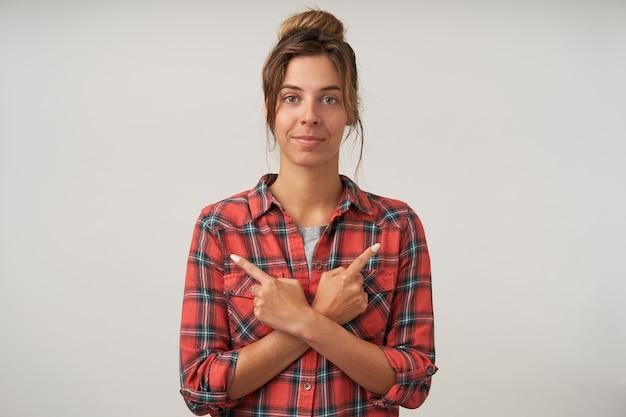 Jonge vrouw poseren op wit met gekruiste handen op haar borst en wijst met wijsvingers naar verschillende kanten met kalm gezicht
