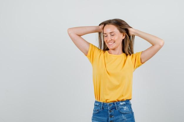Jonge vrouw poseren terwijl hand in hand op het hoofd in t-shirt, korte broek en op zoek charmant. vooraanzicht.