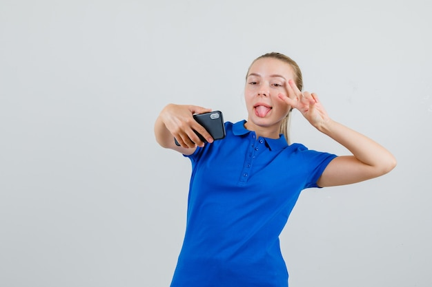 Jonge vrouw poseren terwijl het nemen van selfie in blauw t-shirt en op zoek gek