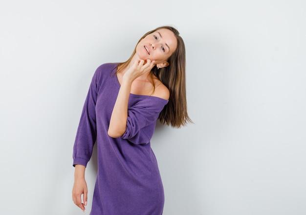 Jonge vrouw poseren terwijl staande in violet overhemd en op zoek charmant, vooraanzicht.