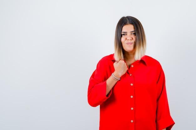 Jonge vrouw poseren terwijl ze in een rood oversized shirt staat en er vrolijk uitziet. vooraanzicht.