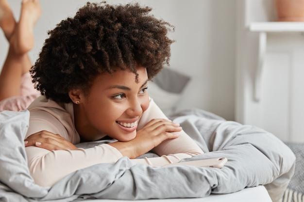 Jonge vrouw poseren thuis in comfortabel bed