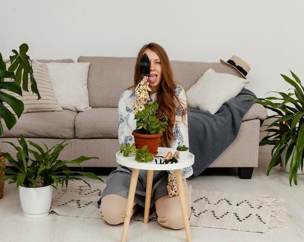 Jonge vrouw poseren thuis met pot van plant en tuinieren tool