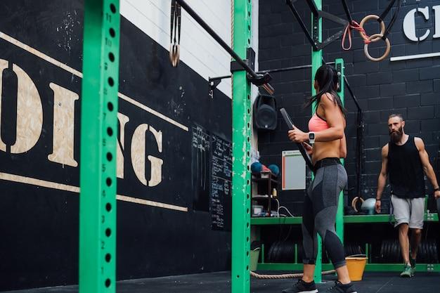 Jonge vrouw power tillen geholpen door haar persoonlijke trainer