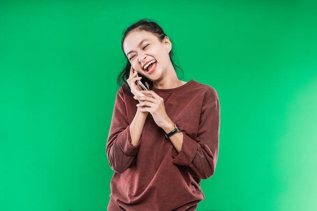 Jonge vrouw praat aan de telefoon en lacht gelukkig met iemand tegen een groene achtergrond