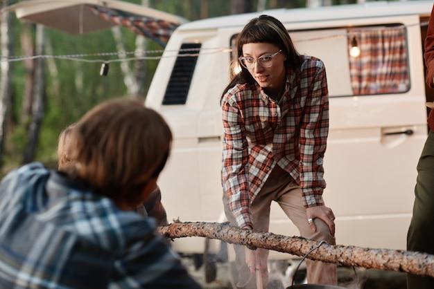 Jonge vrouw praat met haar vriend terwijl ze samen eten koken op een picknick