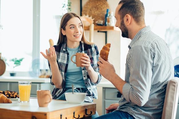 Jonge vrouw praat met haar vriendje bij het ontbijt en gebaart