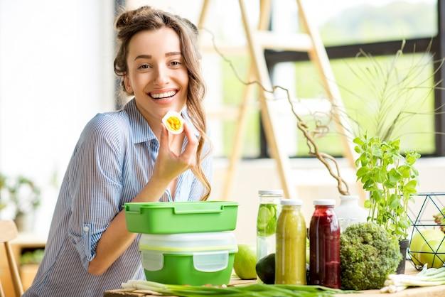 Jonge vrouw prapairing voedsel in groene lunchboxen zittend op de tafel binnenshuis