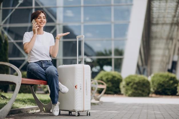 Jonge vrouw praten aan de telefoon op de luchthaven