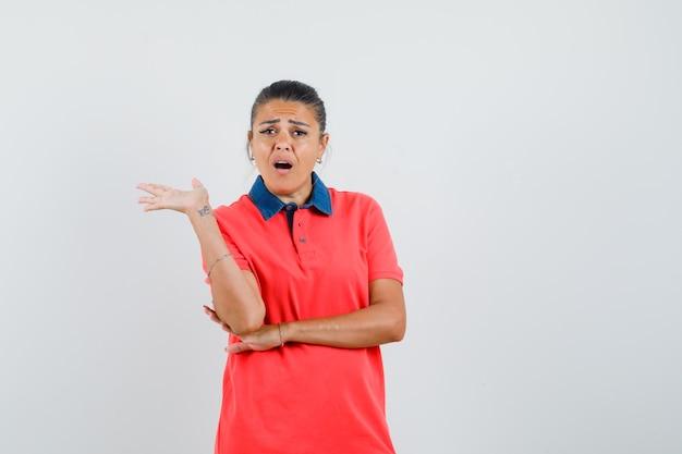 Jonge vrouw praten en strekken palm in rood t-shirt en op zoek nieuwsgierig, vooraanzicht.