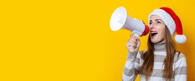 Jonge vrouw praten in een megafoon op een gele achtergrond. banier.