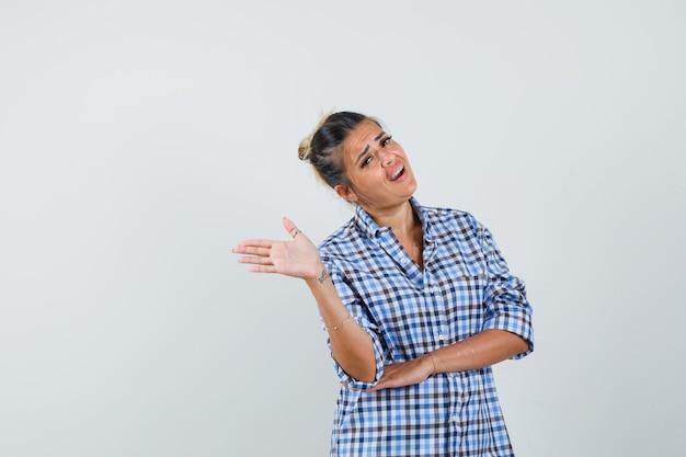 Jonge vrouw praten met iemand terwijl het verspreiden van palm opzij in geruit overhemd en spraakzaam op zoek.