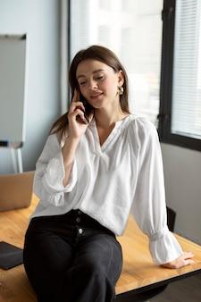 Jonge vrouw praten op de smartphone op het werk