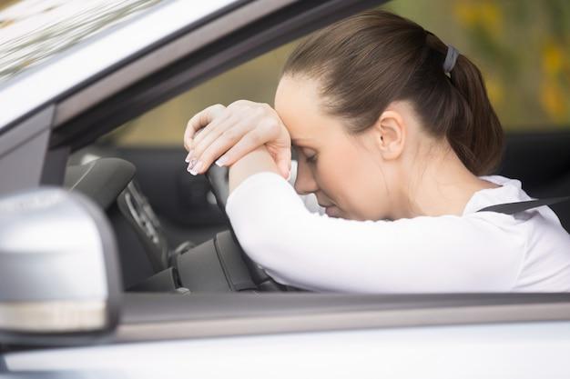 Jonge vrouw praten op haar telefoon rijden een auto