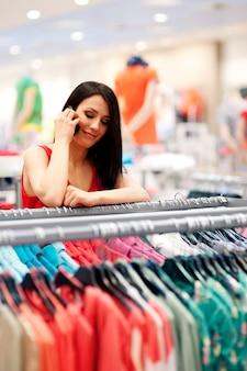 Jonge vrouw praten over de mobiele telefoon in de winkel