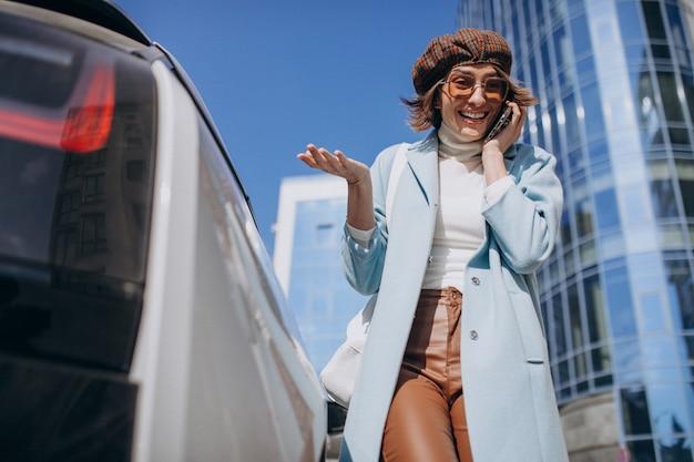 Jonge vrouw praten over de telefoon door electro auto in het centrum
