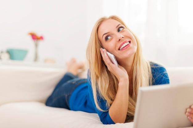 Jonge vrouw praten over de telefoon en digitale tablet te houden