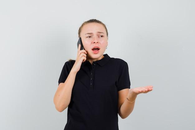 Jonge vrouw praten over de telefoon en haar ene hand in zwart t-shirt opheffen en gefrustreerd kijken