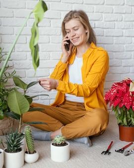 Jonge vrouw praten over de telefoon naast haar plant