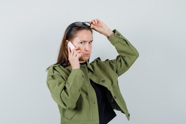 Jonge vrouw praten over de telefoon terwijl het verhogen van de bril boven haar hoofd in groene jas.
