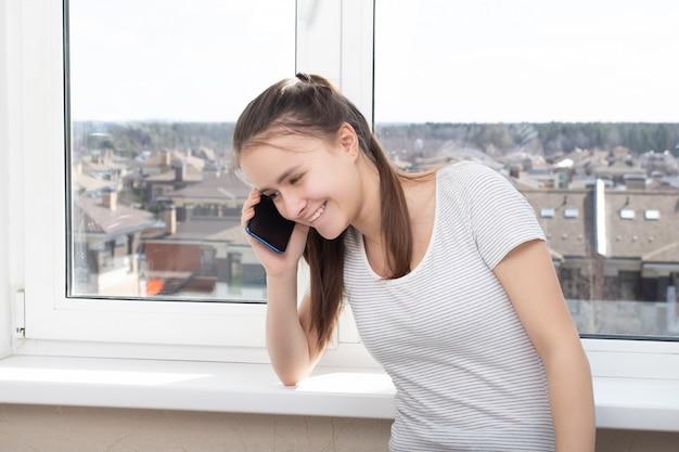 Jonge vrouw praten over de telefoon thuis bij het raam