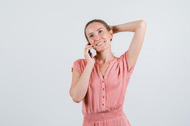 Jonge vrouw praten over mobiel met hand achter hoofd in gestreepte jurk en op zoek blij, vooraanzicht.