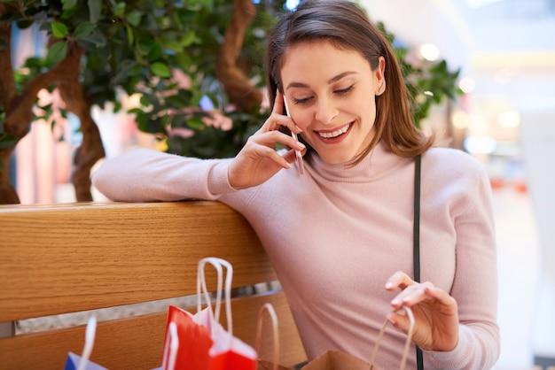 Jonge vrouw praten via de mobiele telefoon na het grote winkelen