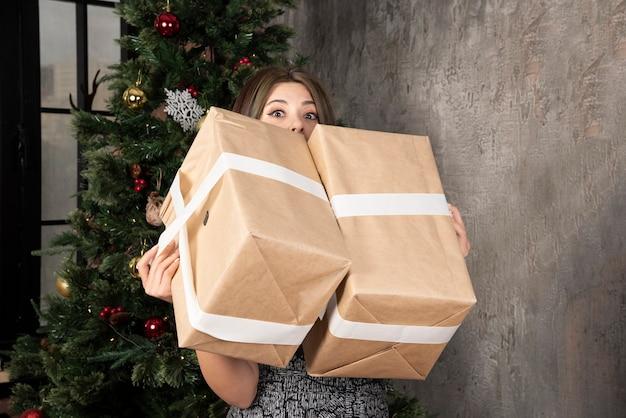 Jonge vrouw presenteert in de hand staande bij de kerstboom