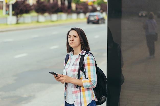 Jonge vrouw probeert een taxi te halen bij een bushalte met een app van een mobiele telefoon