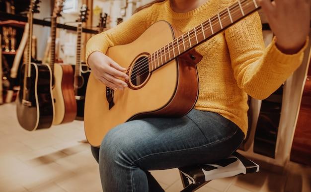Jonge vrouw probeert en koopt een nieuwe houten gitaar in instrumentale winkel of winkel