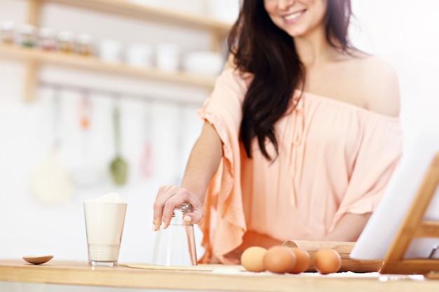 Jonge vrouw probeert pierogi te maken in de keuken