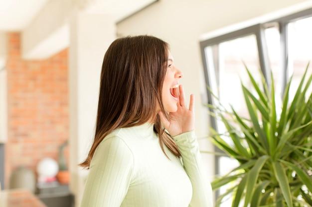 Jonge vrouw profielweergave op zoek blij en opgewonden schreeuwen en roepen om ruimte aan de zijkant te kopiëren