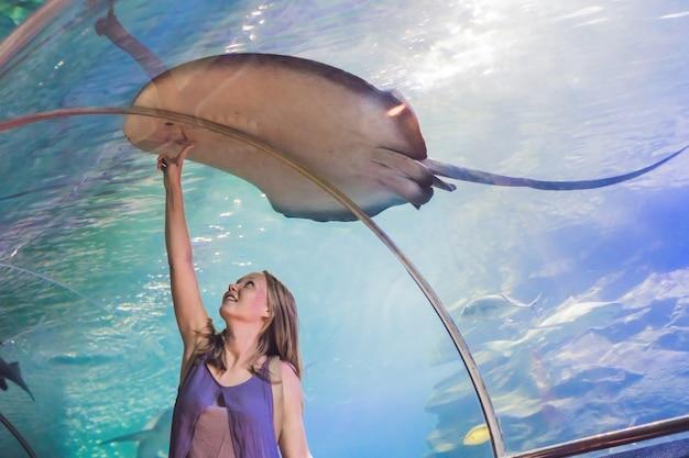 Jonge vrouw raakt een zwemmende pijlstaartrog in de oceanariumtunnel