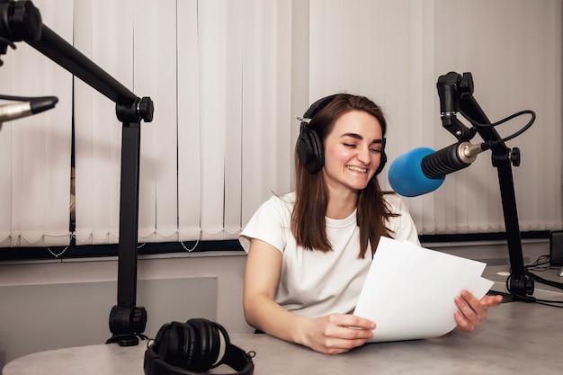 Jonge vrouw radiopresentator in studio met koptelefoon en microfoon en praat nieuws live