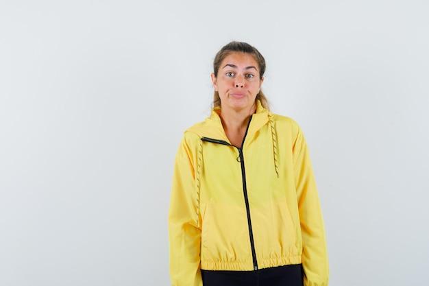 Jonge vrouw rechtdoor en poseren aan de voorkant in gele bomberjack en zwarte broek en schattig op zoek