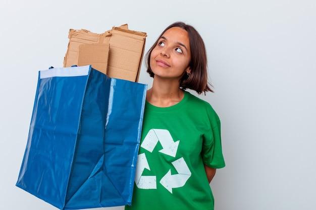 Jonge vrouw recycling karton geïsoleerd op een witte muur dromen van het bereiken van doelen en doeleinden