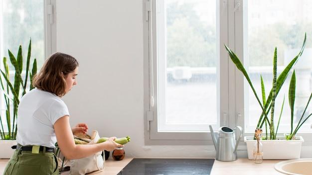 Jonge vrouw regelen biologische groenten in de keuken
