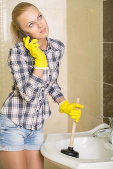 Jonge vrouw reinigt de gootsteen met luchtkleppen.