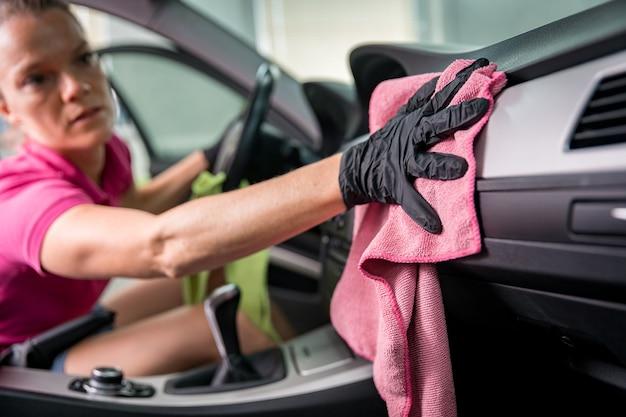 Jonge vrouw reinigt het interieur van het voertuig