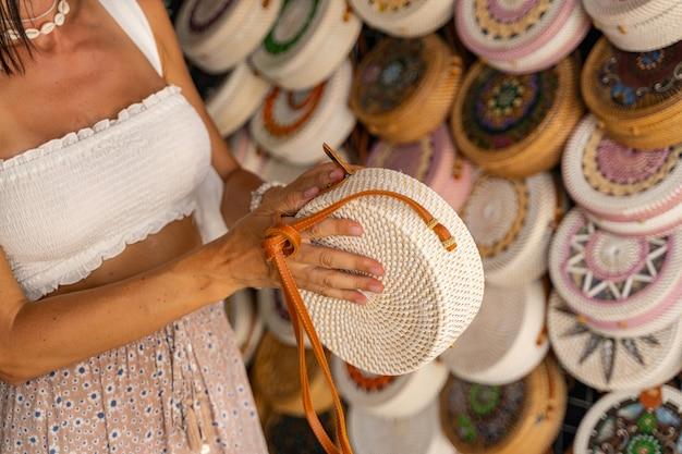 Jonge vrouw reist en koopt handgemaakte souvenirs in de lokale mandenwinkel. lokale marktconcept