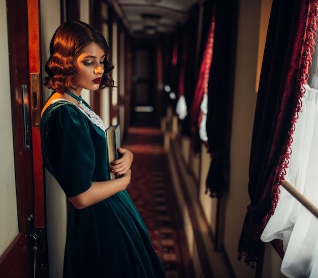 Jonge vrouw reist, vintage treincoupé. oud wagenbinnenland. spoorwegreis, treinreis