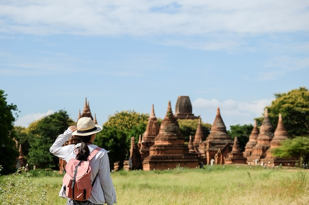 Jonge vrouw reizend backpacker met hoed, aziatische reiziger die mooie oude tempels en pagode, oriëntatiepunt en populair voor toeristische aantrekkelijkheden in bagan, myanmar kijken. azië reizen concept