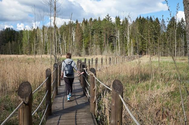 Jonge vrouw reiziger met rugzak heeft een wandeling over een houten brug in natuurgebied